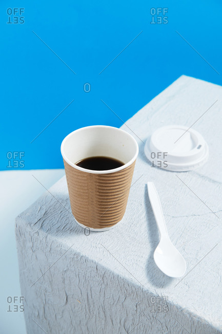 Reusable cup with coffee on white table with white plastic cap and spoon