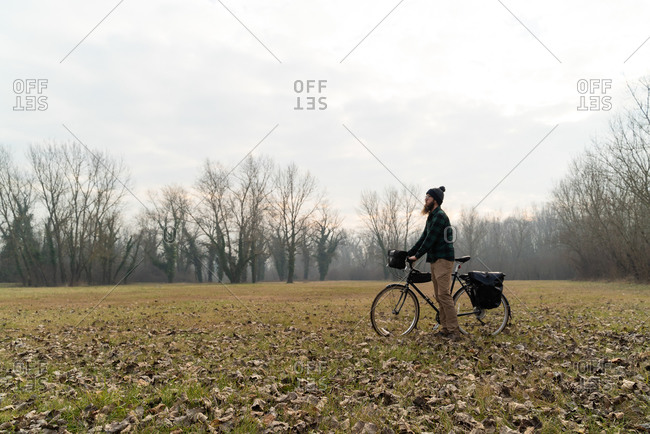 Establishing shot of man pushing touring bicycle at a landscape, Croat