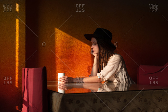 Portrait of young woman in hat sit alone in cafe