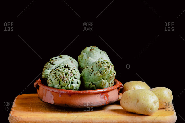 Still life of artichokes and potatoes on a kitchen wooden board