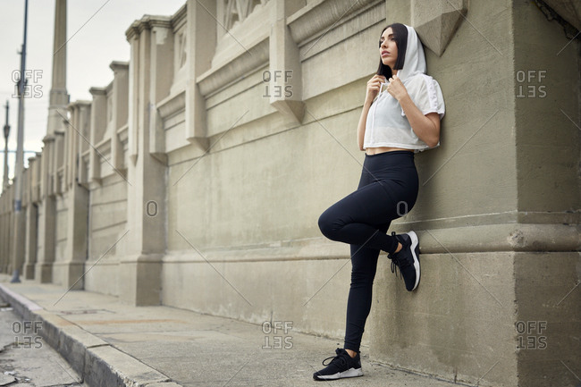 Full length of jogger looking away while standing on sidewalk against wall in city