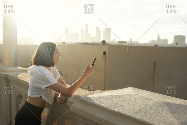 Thoughtful woman using smart phone on bridge during sunny day