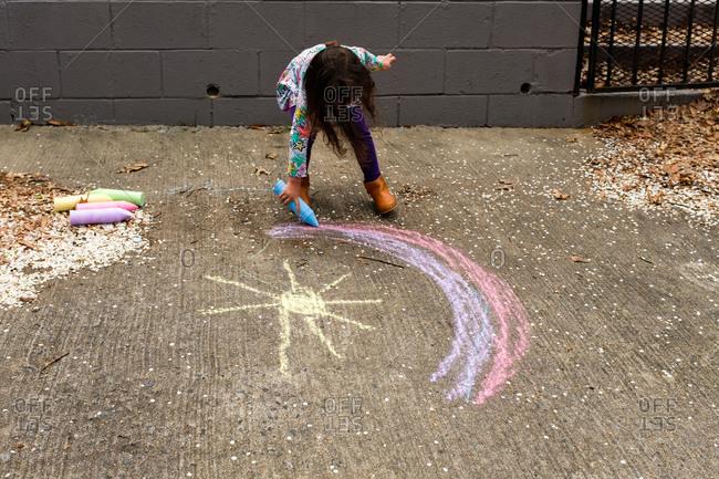 Little girl drawing rainbow with chalk