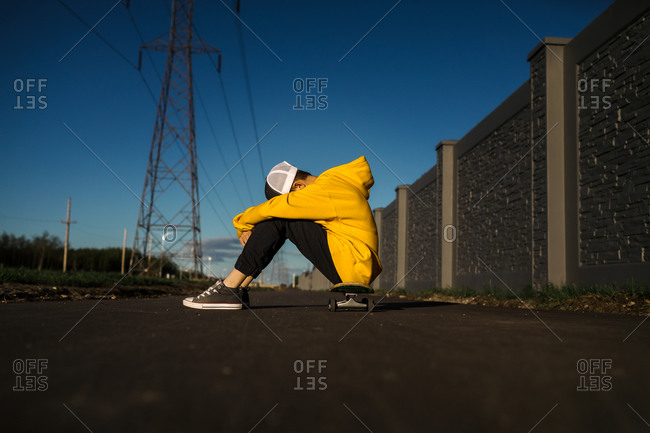 Teen boy with head down sitting on skateboard