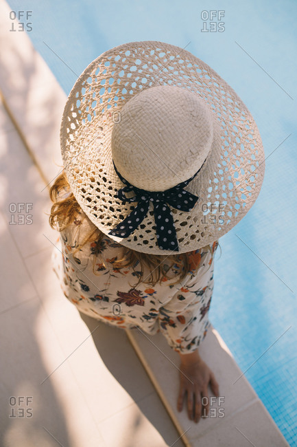 Close up top view of woman with hat sitting by the pool