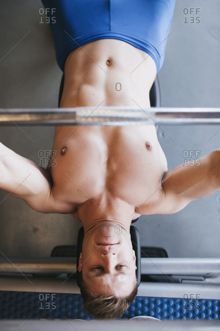 Close up top view of young man on the bench lifting weights