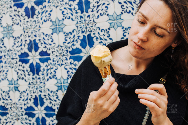 Millennial woman with freckles looking at melting ice cream