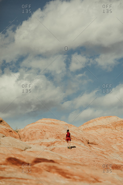 woman hiker walks up a red rock hill towards blue cloudy skies in utah