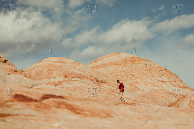 female hiker dressed in red walks up red and white petrified sand dune