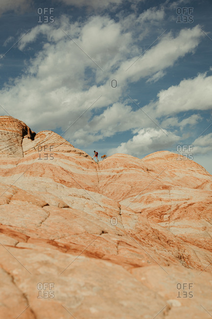 hiker and dog walk in crux of petrified sand dunes on desert horizon