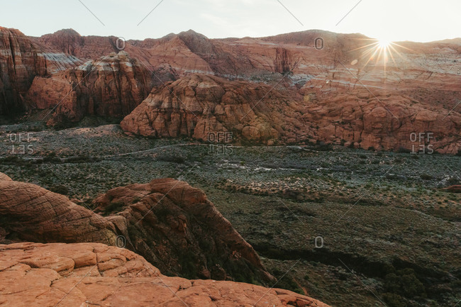 sun sets on red cliffs across valley at Snow Canyon State Park