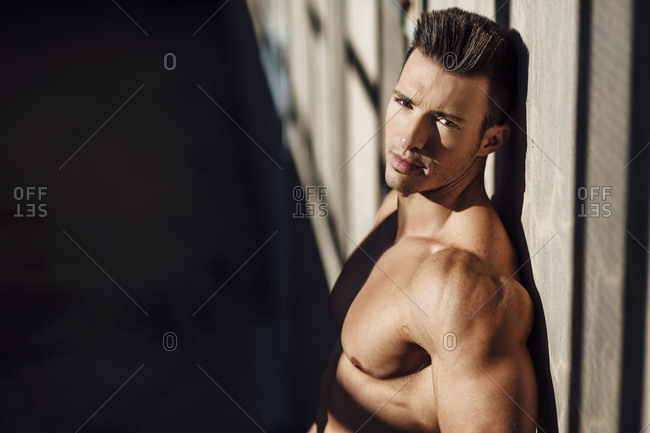 handsome muscular man leaning against the wall looking at camera