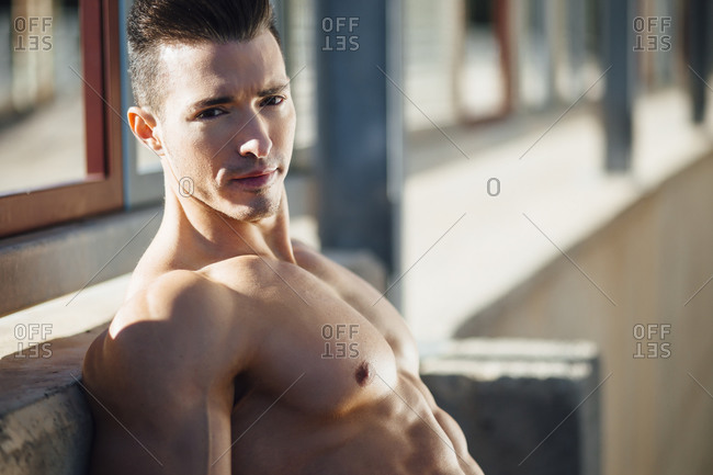 portrait of muscular man leaning on the wall and looking at camera