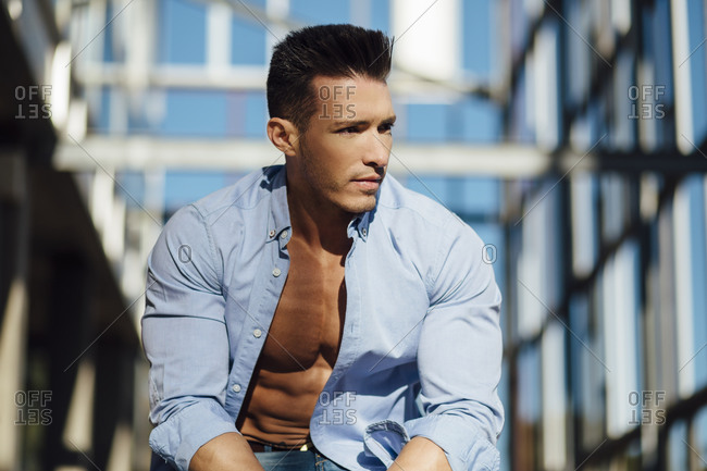 handsome muscular guy with open shirt in modern building