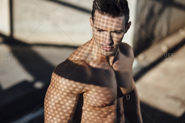 handsome and muscular guy looking down with sun rays on his skin
