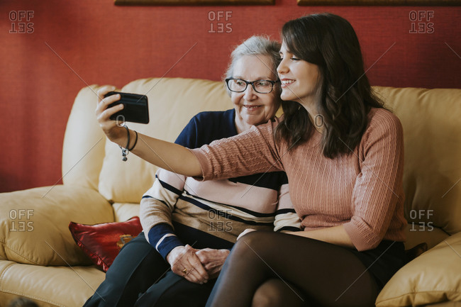 granddaughter and grandmother taking a selfie on the sofa