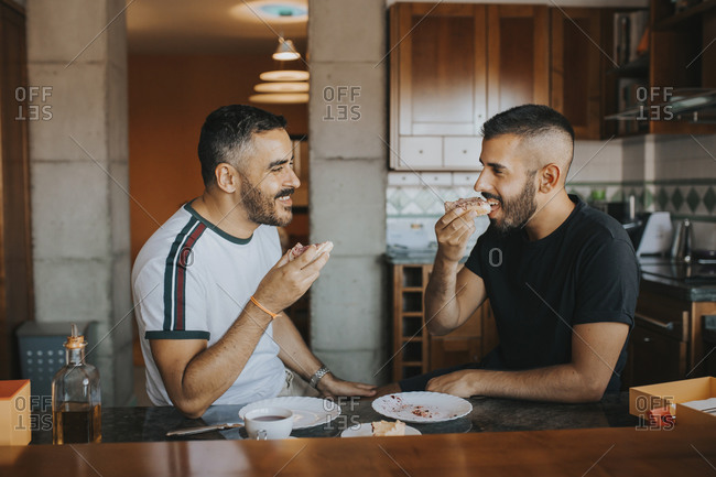 Homosexual couple having breakfast together in the kitchen