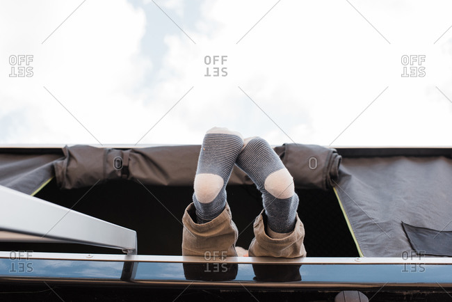 child's feet hanging out of a roof top tent whilst camping