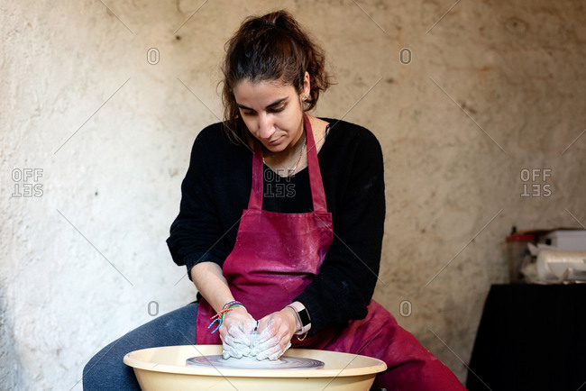 Ceramist artist female working in her atelier with The Pottery Wheel