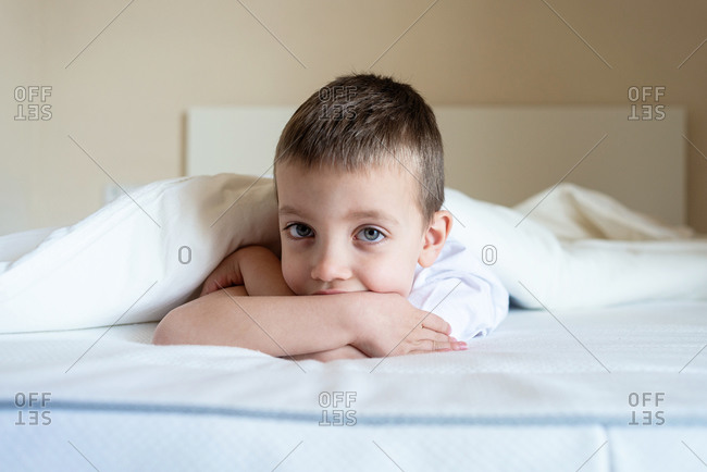 Adorable kid lying down on bed under blanket, while looking camera