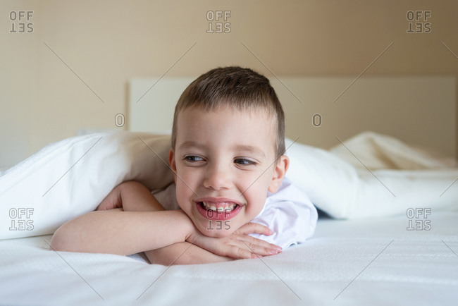 Adorable smiling kid lying down on bed under blanket, looking camera