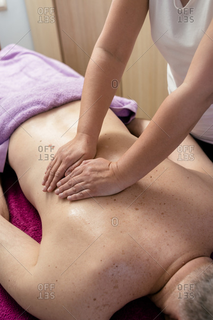 Female masseuse massaging a male patient's back