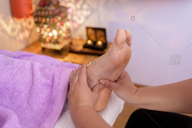 Female therapist giving a foot reflexology massage to a man