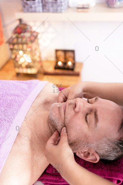 Female masseuse massaging a male patient's face