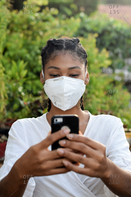 Young black woman in face mask using a smartphone