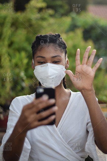 Young black woman in face mask doing a video call