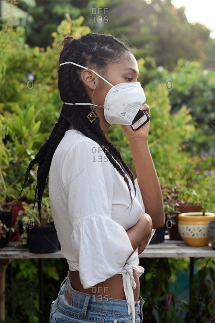 Young black woman in face mask speaking on the phone