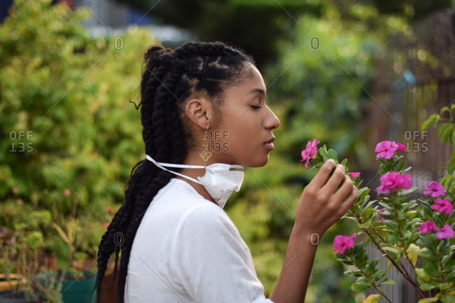Young woman takes face mask off to smell the flowers