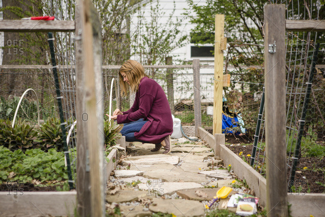 A woman plants seeds in her garden while child plays in background