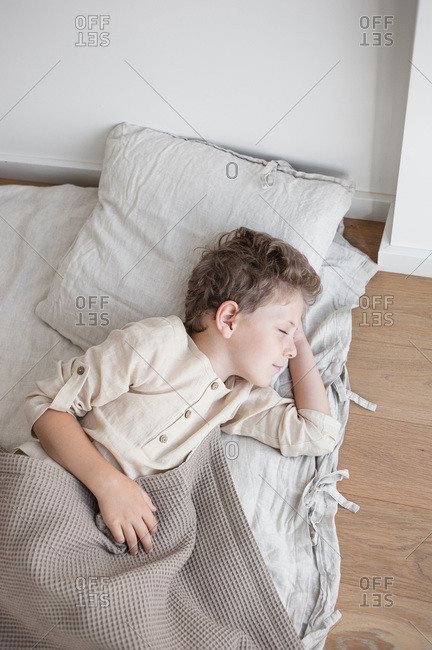 Boy in linen clothes sleeps in natural linen covered bed daytime.