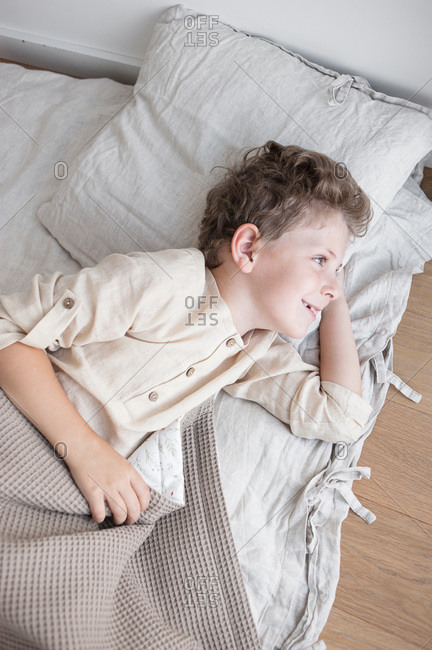 Boy in home clothes joyfully lies in natural bedding after waking up.
