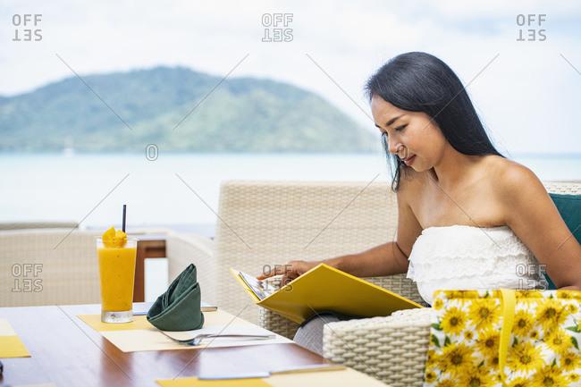 Woman checking the menu at restaurant in luxury resort in Phuket