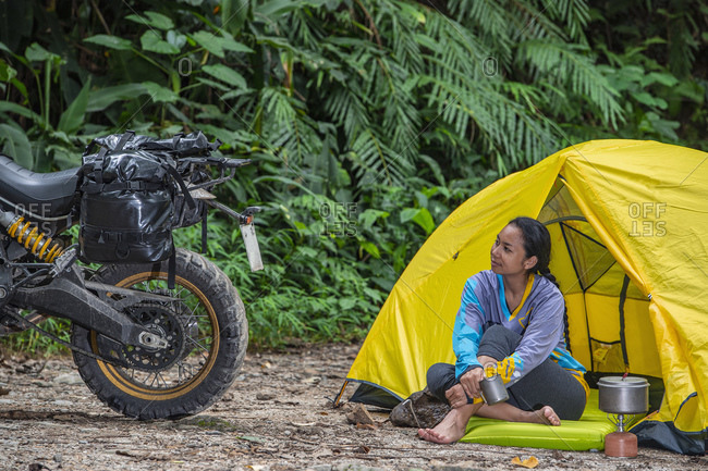 woman relaxing at camp looking at her scrambler type motorcycle