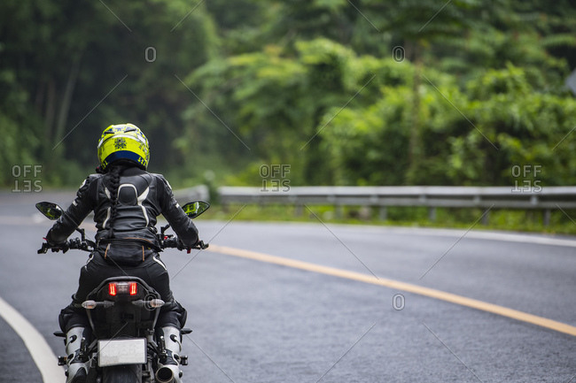 woman riding her motorcycle on empty highway in Thailand