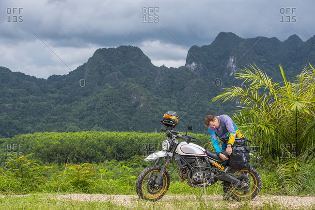 man packing his scrambler type motorcycle in the mountains of Thailand