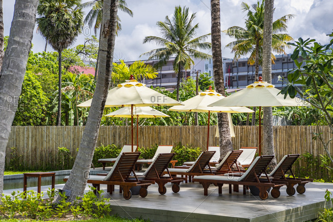 Sun lounge chairs and parasol's at luxury holiday resort in Phuket