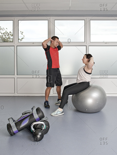 personal trainer helping client at gym in the UK