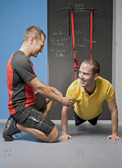 personal trainer helping client with suspension training in gym