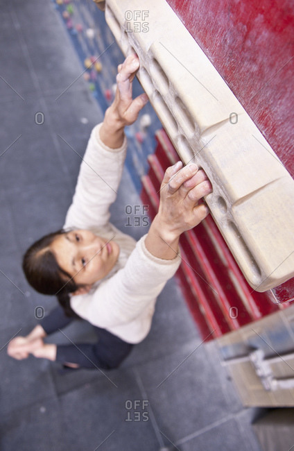 Woman training on fingerboard at indoor climbing gym