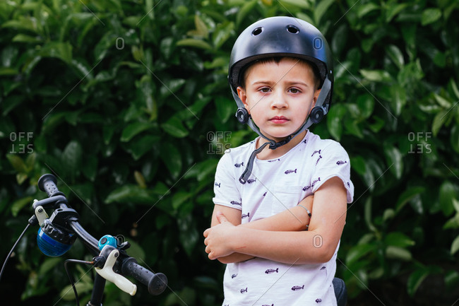 portrait of a 4 year old boy, sitting on his bike on a green background