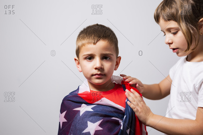 6-year-old girl wrapping the U.S. flag around her 4-year-old brother