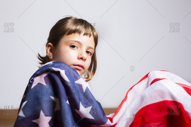 Beautiful portrait of a 6-year-old blonde girl wrapped in the American flag