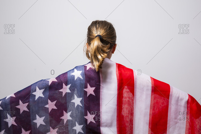 Portrait of an anonymous blonde girl, 6 years old, wrapped in the American flag