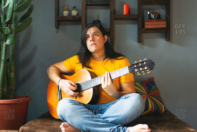Man with long hair playing guitar at home in chill place pandemic time