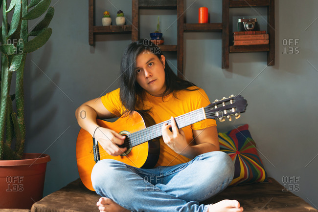 man with long hair playing acoustic guitar at home during quarantine