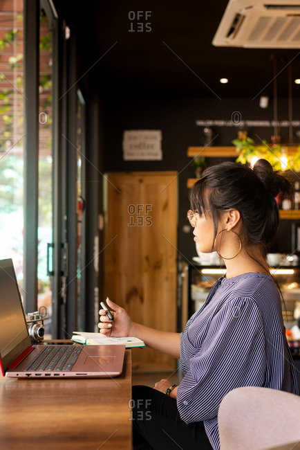 Girl having coffee while working in a cozy environment